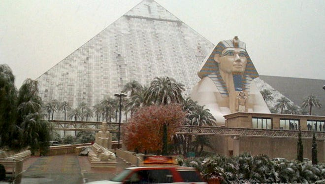 Snow covers the sides and sphinx of the Luxor Hotel on the Las Vegas Strip on Dec. 17, 2008. If Sin City's sports books took bets on the weather, snow in Las Vegas on New Year's Eve would normally have terrible odds. It might pay out for 2014, though, if the white flurries start falling on an Eiffel Tower, a pyramid and a volcano come Wednesday night, Dec. 31, as forecast by the National Weather Service.