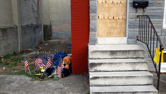 In this Nov. 27, 2017, file photo, a makeshift memorial sits in an alley where Baltimore Police Detective Sean Suiter was shot while investigating a 2016 triple homicide in Baltimore. The unsolved slaying of a homicide detective haunts the Baltimore Police Department. More than three months have passed since an on-duty attack killed Suiter a day before he was set to testify before a grand jury investigating dirty cops. Investigators have come up empty-handed.