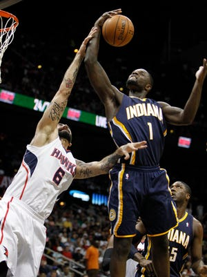 Indiana Pacers guard Lance Stephenson grabs a rebound over Atlanta Hawks center Pero Antic in the first quarter Thursday in Atlanta.