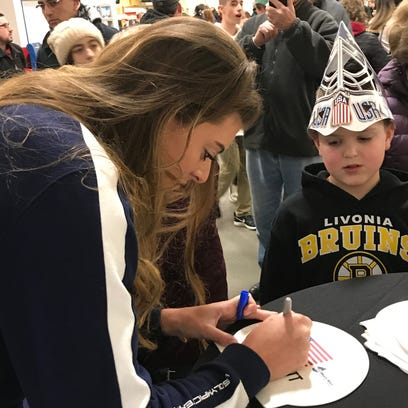 Allison Schmitt signs a swim cap for 9-year-old Colin