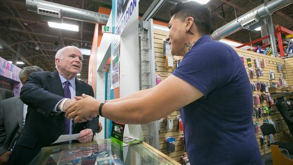 Sen. John McCain, R-Ariz., shakes hands with a vendor
