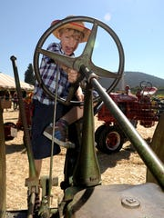 Max Coy of Los Angeles plays on an old tractor on display during the 2014 Antique Tractor Weekend at Underwood Farms in Moorpark.