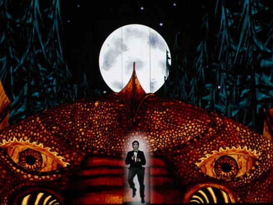 Tamino (Aaron Blake) runs from a dragon in the opening scene of Cincinnati Opera's production of Wolfgang Amadeus Mozart's The Magic Flute.