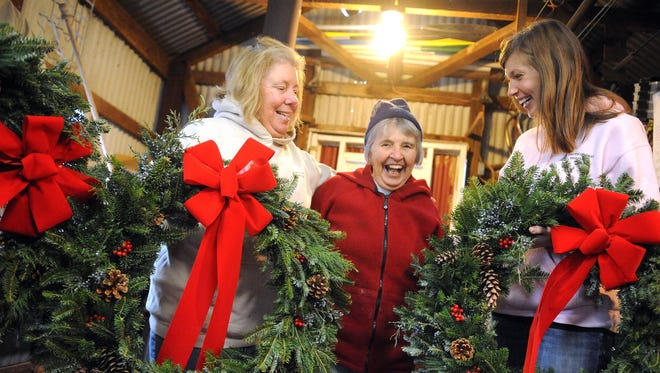 Holding wreaths destined for northern Virginia, Bev Coffman and Ashley Coffman of Carter Coffman Tree Farm look to Bev's mother, Kit Carter, while on the farm near Fort Defiance on Sunday, Dec. 12, 2010. As a nonprofit foundation responsible for maintaining the U.S. Marine Corps Memorial in Arlington, the Marine Corps War Memorial Foundation collected wreaths from three local tree farms to be displayed on the memorial, also known as the Iwo Jima Memorial.