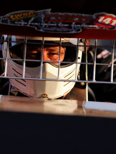 Sprint car driver Scott Sippel of Elkhart Lake appears focused as he finishes getting strapped into a two-seater sprint car owned by Mark Jens of Manitowoc at the 2014 Manitowoc County Fair on Wednesday, Aug. 20, 2014 at the Manitowoc County fairgrounds in Manitowoc. Matthew Apgar/HTR Media