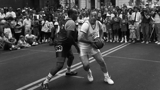 Gov. Mario Cuomo, right, takes on state Assemblyman David Gantt in a one-on-one basketball game on Main Street in Rochester during the 1990 Jumpin' Jack Shootout.