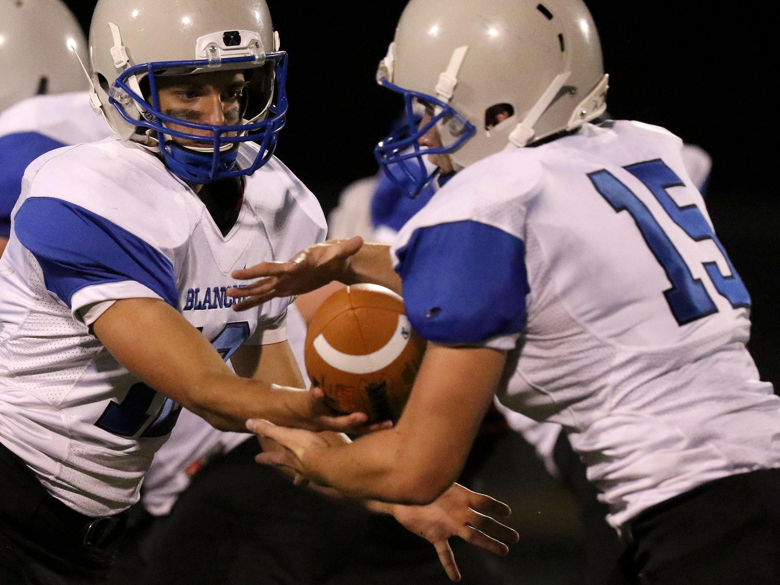 Blanchet quarterback R.J. Veil hands the ball off to Denver Bogat during their game with Scio on Sept. 18.