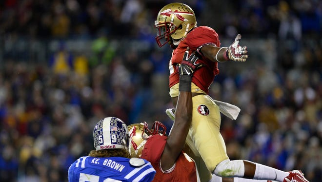 Florida State running back Karlos Williams (9) is lifted into the air by offensive lineman Cameron Erving (75) after scoring a touchdown in the second quarter Saturday in the ACC Championship. Florida State next will play for the national title.