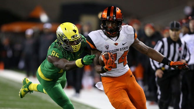 Oregon State's Storm Woods runs under pressure from Oregon's Torrodney Prevot (86) during the Civil War game on Saturday, Nov. 29, 2014, in Corvallis, Ore.