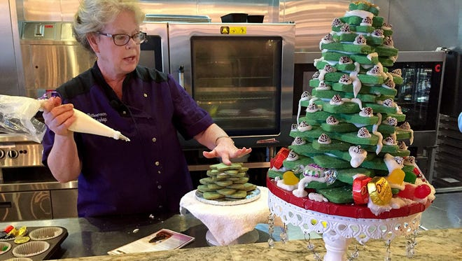 Marsha Hogerheide gives a demonstration on how to build a Sugar Cookie Cut Out Christmas Tree. Hogerheide owns and runs Buttercream Bakeshop in Wixom. The cookie tree can be a holiday centerpiece or given as a gift.