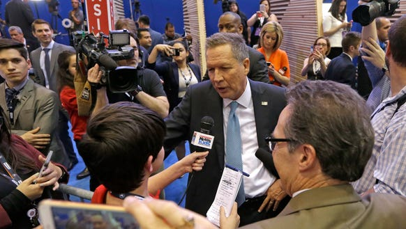 John Kasich talks to reporters in the media spin room
