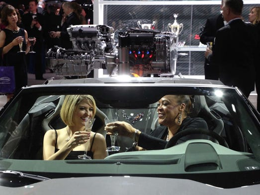 Women toast while sitting in a Corvette in the Chevrolet