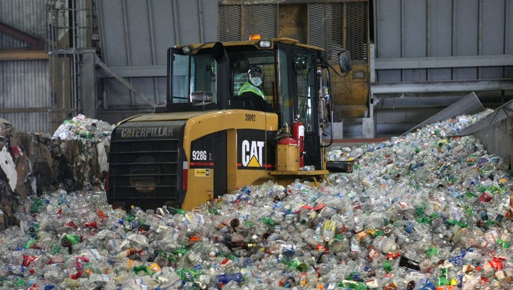A tractor drives through a giant pile of plastic bottles