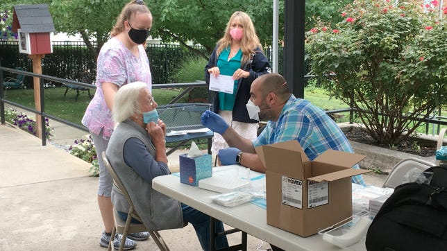Joey Thomas, Hearthstone Administrator, and Trish Williams, Registered Nurse, observe Jonathan Horn of WorkNet Occupational Medicine administering a COVID test to Mrs. Moyer, one of 26 residents of Hearthstone Retirement Home and In-Home Care Services. PROVIDED PHOTO