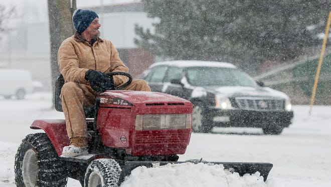 Bryan Snyder uses a tractor with a plow to clear a sidewalk Sunday morning February 1, 2015. Forecasts call for snow throughout the day.