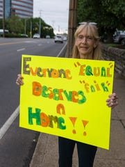 Prestige Pointe resident Anna Holt holds up a sign