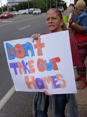 "Lucinda Sharp holds up her ""Don't take our homes"" sign"