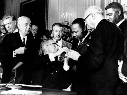 U.S. President Lyndon B. Johnson reaches to shake hands with Dr. Martin Luther King Jr. after presenting the civil rights leader with one of the 72 pens used to sign the Civil Rights Act of 1964 in Washington, D.C., on July 2, 1964. Surrounding the president, from left, are, Rep. Roland Libonati, D-Ill., Rep. Peter Rodino, D-N.J., Rev. King, Emanuel Celler, D-N.Y., and behind Celler is Whitney Young, executive director of the National Urban League.