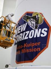 Technicians Install New Horizons Mission Strip