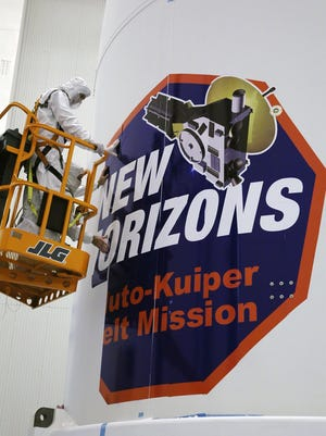 Technicians install strips of the New Horizons mission decal on the spacecraft fairing prior to launch from Cape Canaveral Air Force Station.