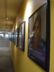 Pictures of exonerees hang on a wall at the Bluhm Legal