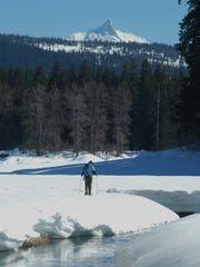 Scott Hovis snowshoes at Fish Lake with Mount Washington in the background.