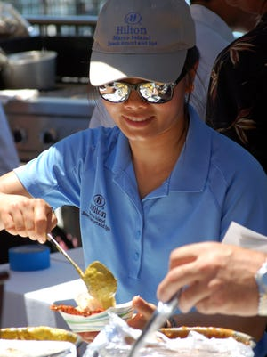 Ping Chen serves chicken tikka at the Hilton resort table.