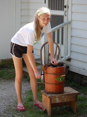 A girl makes ice cream at a Wade House event.