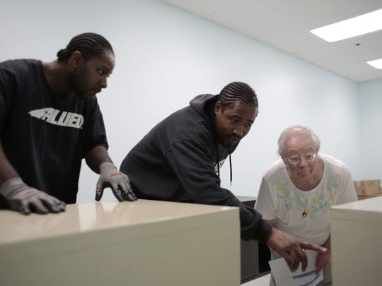 From left, Andree Howard and Eric Foster, both from Detroit, help Sister Rita Sieg from Detroit figure out placement of filing cabinets on Friday, Sept. 26, 2014, at the Dominican Literacy Center in Detroit.