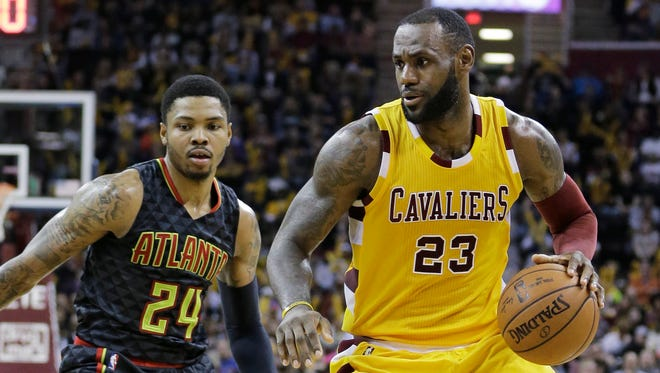 Cleveland Cavaliers' LeBron James (23) drives past Atlanta Hawks' Kent Bazemore (24) in one of their games this season.