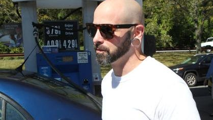 Christopher Perino of Bronxville talks about the price of gasoline while filling his tank at a Mobil station in Harrison Sept. 26, 2014.
