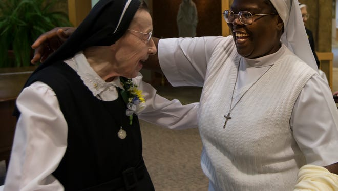 One of the original residents of Franciscan Courts, Sister Frances Meyer, (left) of the Sisters of the Sorrowful Mother moved from Milwaukee's Mother House to Oshkosh twenty-five years ago receives greetings from Sr. Angela and the Catholic community celebrating an anniversary October 14, 2014.