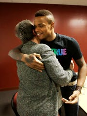 University of Massachusetts basketball guard Derrick Gordon hugs UMass professor emeritus Pat Griffin after speaking to reporters on the school's campus on April 9, 2014, in Amherst, Massachusetts. Gordon became the first openly gay player in Division I men's basketball. Griffin teaches lesbian, gay, bisexual, and transgender issues.