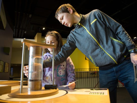 Siblings play with magnets at the Science Center of Iowa.