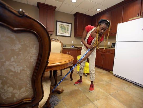 Jennifer Harvey, 23, cleans a dining area at Safe House