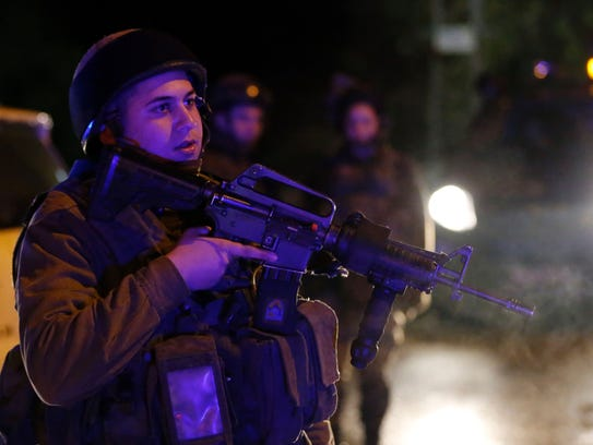 An Israeli soldier stands guard at the site of a stabbing