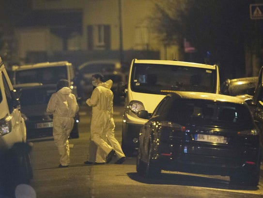 Forensic investigators take part in a police raid in