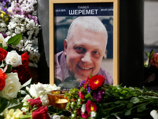 A portrait of journalist Pavel Sheremet is surrounded with flowers and candles in Kiev, Ukraine, after he was killed July 20, 2016.