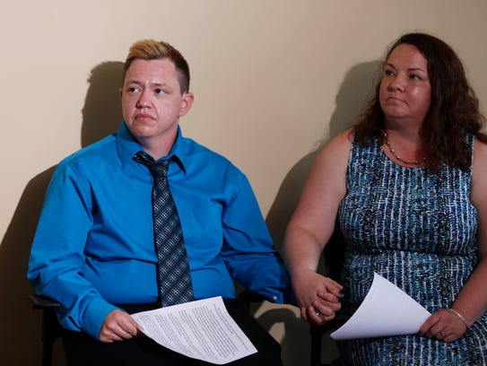 Jesse Vroegh holds the hand of his wife, Jackie, Thursday,