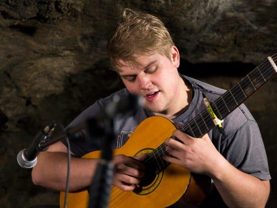 Curt Oren plays guitar inside a cave at Maquoketa Caves