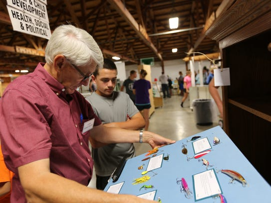 Judge Jim Barthel looks over a fishing display project