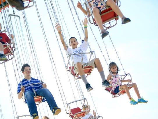 Kids swing from high above the Mountain State Fair