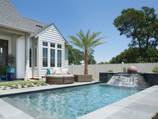 Outdoor living space surrounds the luxurious pool.