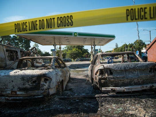Cars stand burned in the lot of the BP gas station