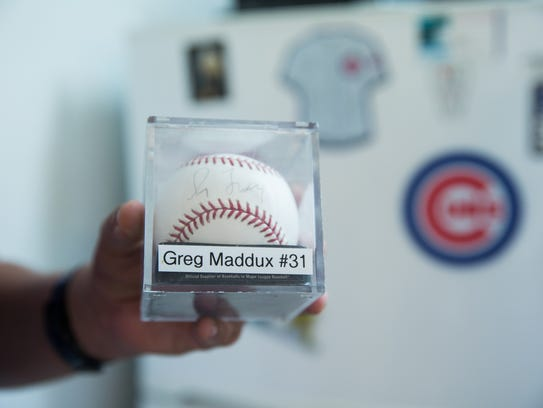 Zach Mirabal, holds up a baseball signed by Greg Maddux.