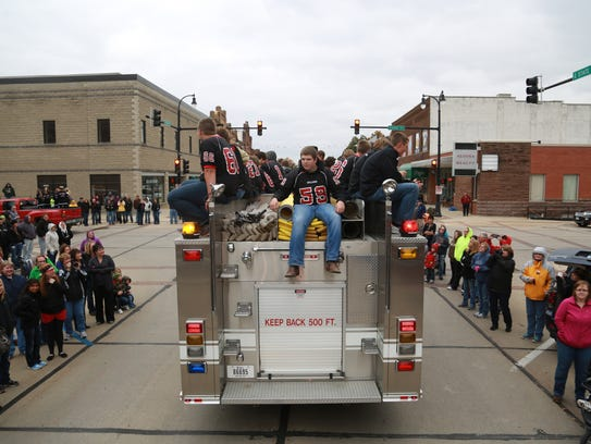 Football players ride on a fire truck during Algona