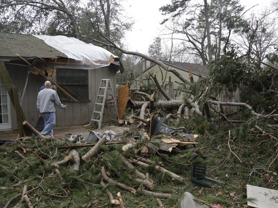 Rick Laurenzo shows off the damage from a tree that