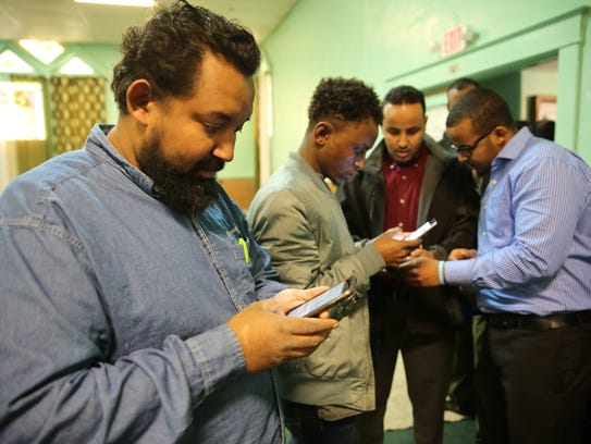 Mohamoud Saidi, from Somalia, signs a petition on his