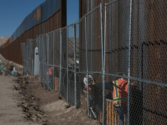 Workers continue work raising a taller fence in the