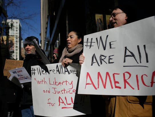 Demonstrators hold up signs during an interfaith solidarity